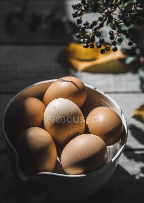 Vista de perto de ovos castanhos em prato perto de bagas frescas em tábua de madeira — Fotografia de Stock