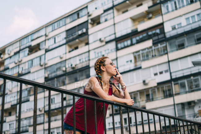 Red-haired young woman with braids and sunglasses smoking against residential building — Stock Photo