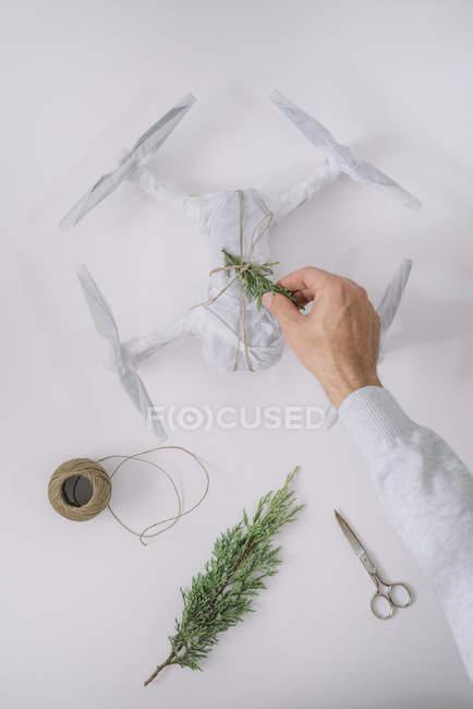 Mão masculino decoração envolta drone como presente de Natal com ramo de abeto e cordéis sobre fundo branco — Fotografia de Stock