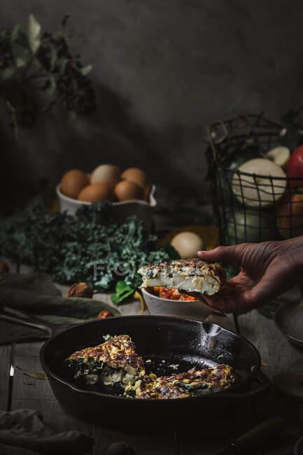 Vue de la main avec tortilla savoureux sur la casserole près des assiettes avec des tranches, tomates, fruits, noix et feuilles sur panneau de bois — Photo de stock