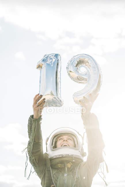 Felice donna in casco e tuta spaziale in posa con il numero 19 contro il cielo — Foto stock