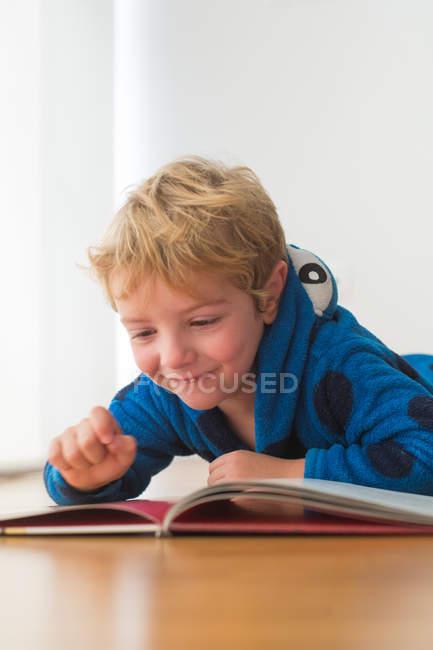 Sourire blond petit garçon lecture livre sur plancher de bois — Photo de stock