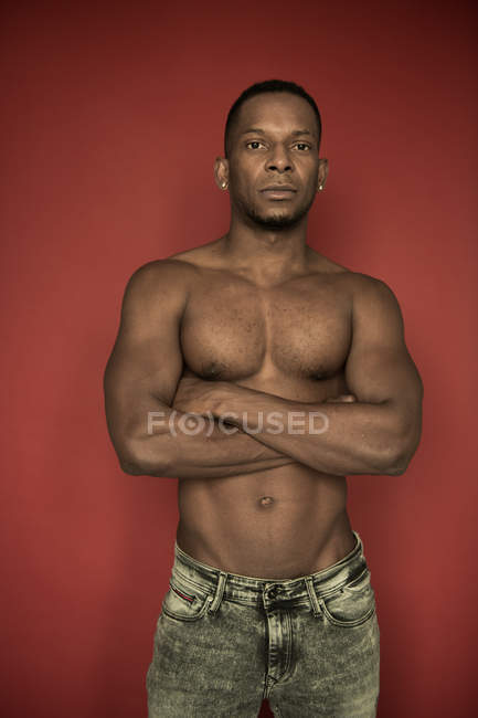 Confident shirtless African American man in denim standing with arms crossed looking at camera on red background — Stockfoto