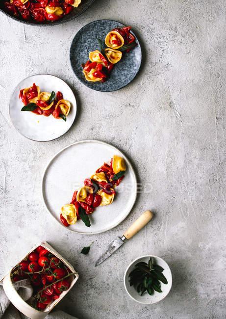 Плиты служили тортеллини с помидорами на серый настольные — стоковое фото
