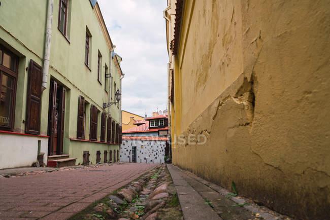 Pavé de briques entre les vieux bâtiments rue étroite de la petite ville — Photo de stock