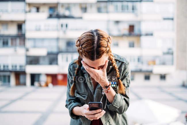 Rothaariges Mädchen mit Zöpfen mit Handy und verdeckt Gesicht mit der Hand gegen Wohnhaus — Stockfoto