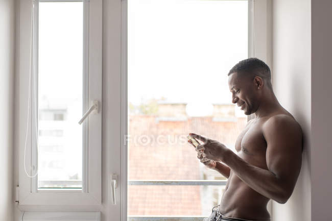 Smiling muscular black man using phone while standing against window in daylight — Stock Photo