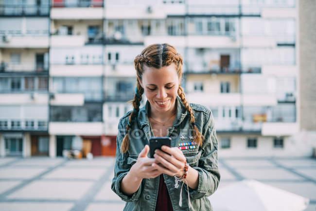 Fille aux cheveux roux souriant avec des tresses en utilisant un téléphone mobile contre le bâtiment résidentiel — Photo de stock