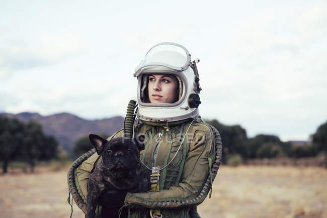 Девушка в старом космическом шлеме держит собаку на природе — стоковое фото