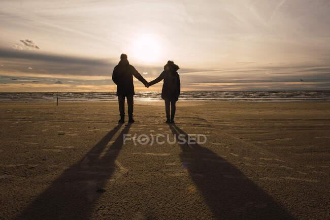 View of couple in outwear standing on sandy beach in cold season holding hands in back lit — Stock Photo