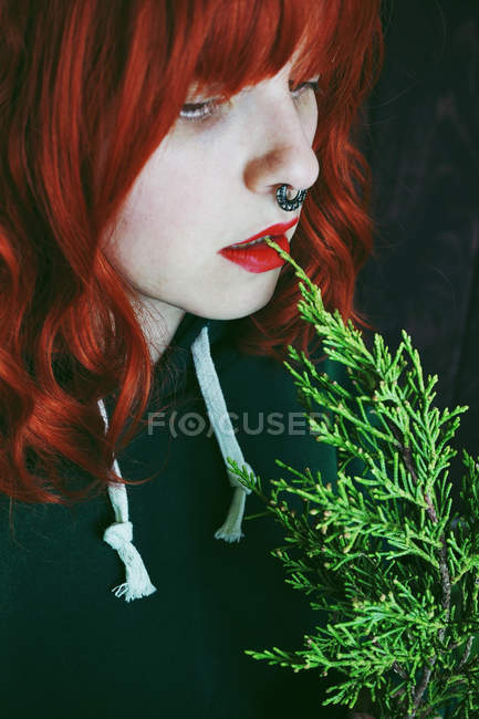Close-up of young red haired woman biting fir twig — Stock Photo