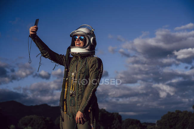 Smiling female astronaut taking selfie mobile phone in evening nature — Stock Photo