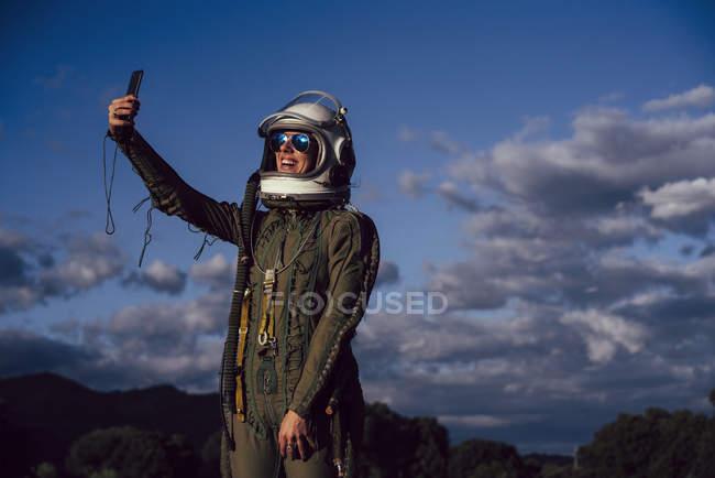 Astronauta sonriente tomando selfie teléfono móvil en la naturaleza de la noche - foto de stock