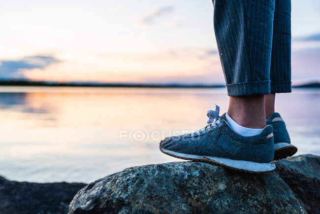 Crop side view of feet of person standing on stone near still lake on background of clear sky — Stock Photo
