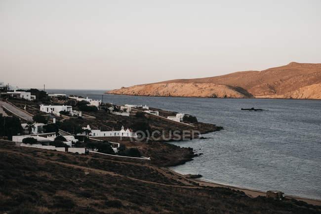 Мальовничий вид білими будинками на узбережжі і човен плаває на воді в Міконос, Греція — стокове фото