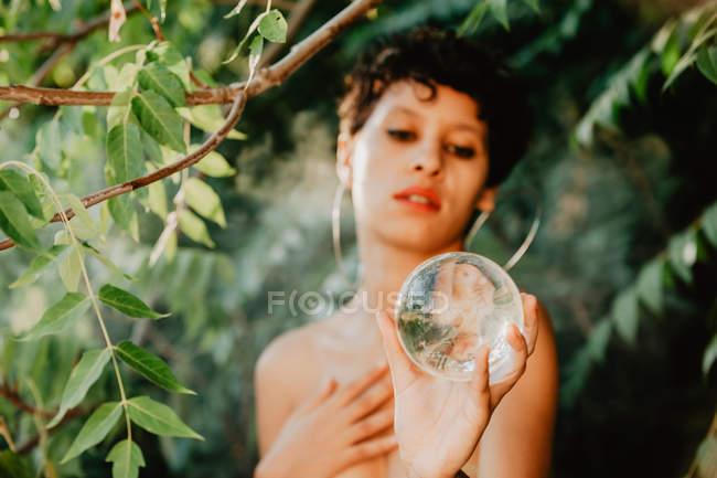 Молодая брюнетка топлесс покрывает грудь и держит прозрачный стеклянный шар в зеленых лесах — стоковое фото