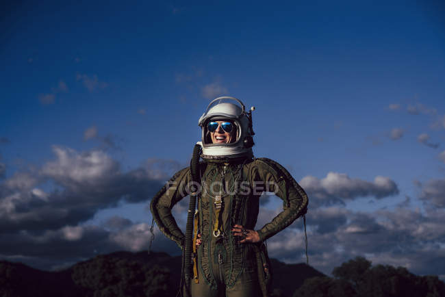 Confident happy female astronaut standing in nature in evening — Stock Photo