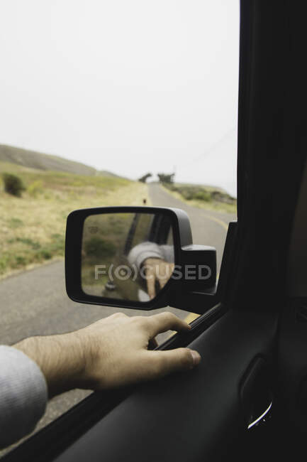 Hand of anonymous man lying on car window near wing mirror during amazing trip through beautiful countryside — стокове фото