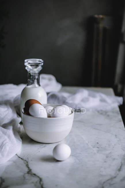 Schüssel mit Hühnereiern und Flasche frischer Milchprodukte steht auf Marmortischplatte in der Küche — Stockfoto