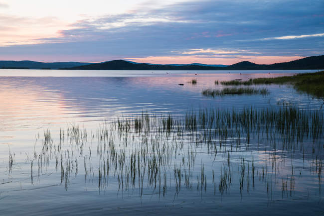 Surface of tranquil blue lake with cloudy sky at sunset, Lapland — Stock Photo