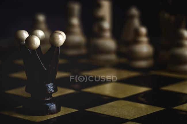 Primo piano di pezzi di gioco e scacchi su sfondo scuro — Foto stock