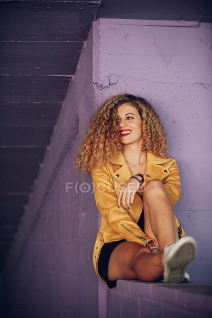 Trendy smiling curly woman in bright yellow jacket sitting on purple brick wall — Stock Photo