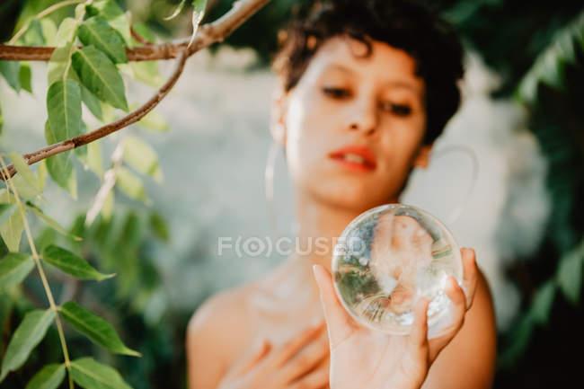 Молодая брюнетка топлесс, охватывающих груди и проведение стеклянный прозрачный шар в зеленых лесах — стоковое фото