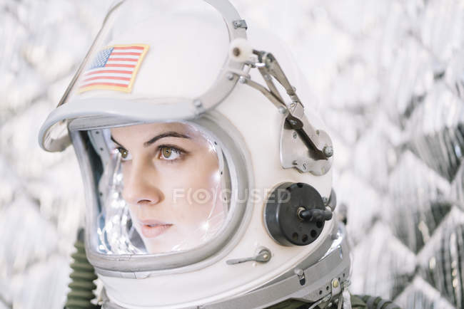 Girl wearing old space helmet with american flag sign — Stock Photo