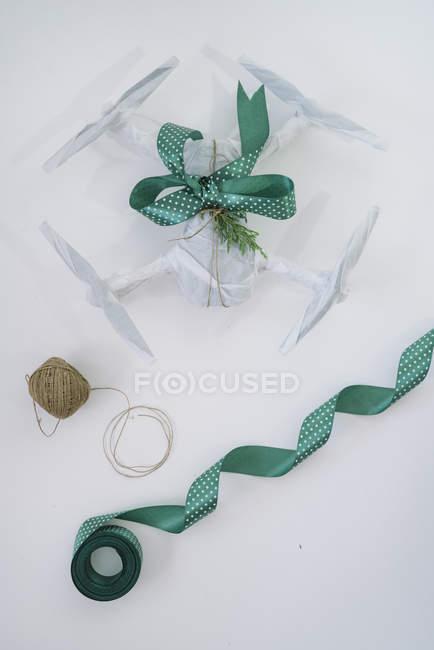 Drone embrulhado como presente de Natal com fita verde sobre fundo branco — Fotografia de Stock