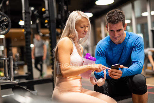 Athletic man and woman using smartphone in gym — Stock Photo