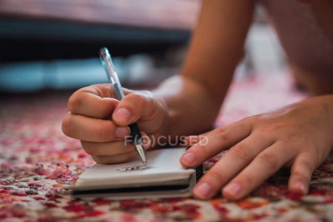 Закри жіночих рук, писати в ноутбук на поверсі — стокове фото