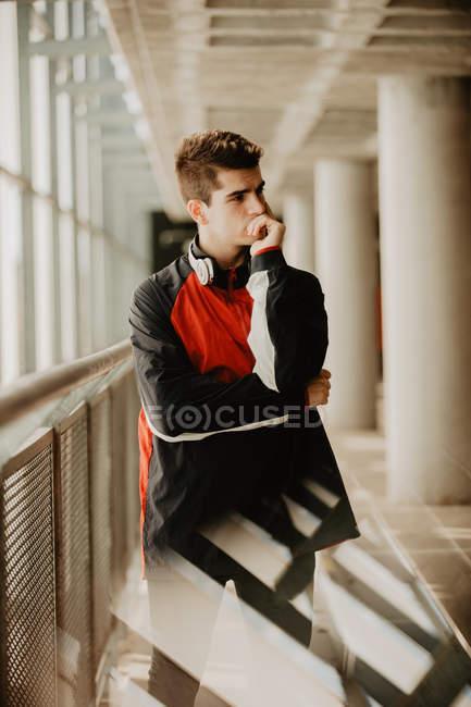 Giovane uomo premuroso in piedi dentro edificio con pilastri — Foto stock