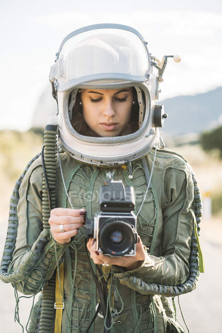 Girl wearing old space helmet and spacesuit holding photo camera outdoors — Stock Photo