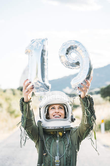 Happy woman in helmet and spacesuit posing with number 19 against sky — Stock Photo