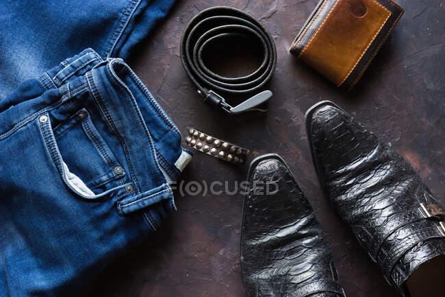 Vista aérea da roupa jeans mens com carteira, pulseira tack, smartphone. e sapatos de couro preto — Fotografia de Stock