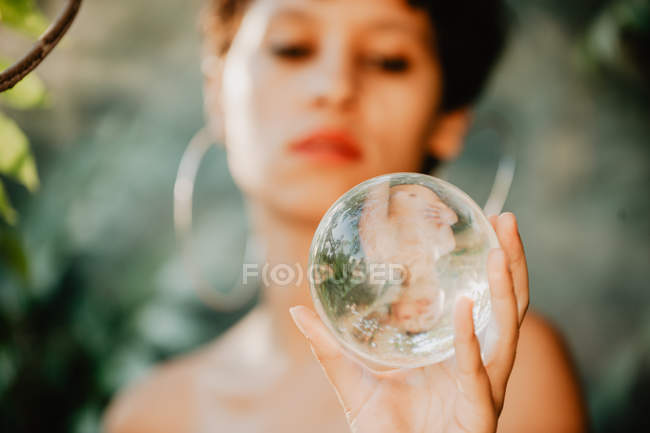Young topless brunette woman holding glass transparent ball in green woods — Stock Photo