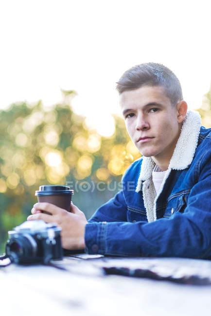 Jovem sentado ao ar livre com sua câmera — Fotografia de Stock