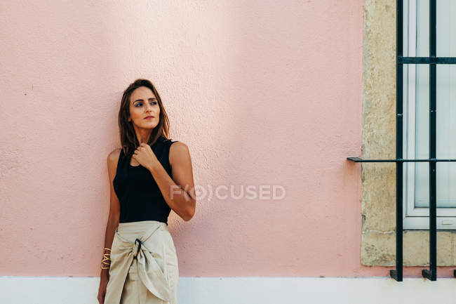 Charming brunette woman in trendy outfit leaning on wall on street and looking away — Stock Photo
