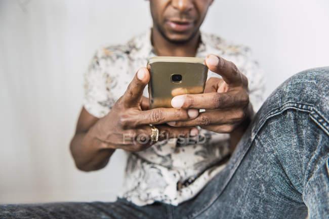 Fechar-se de telefone celular moderno brilhante em mãos de homem preto sentado contra a parede branca — Fotografia de Stock