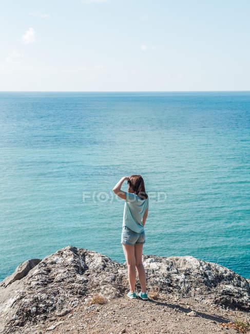 Mulher de pé em penhasco rochoso sobre o mar e olhando para a vista — Fotografia de Stock