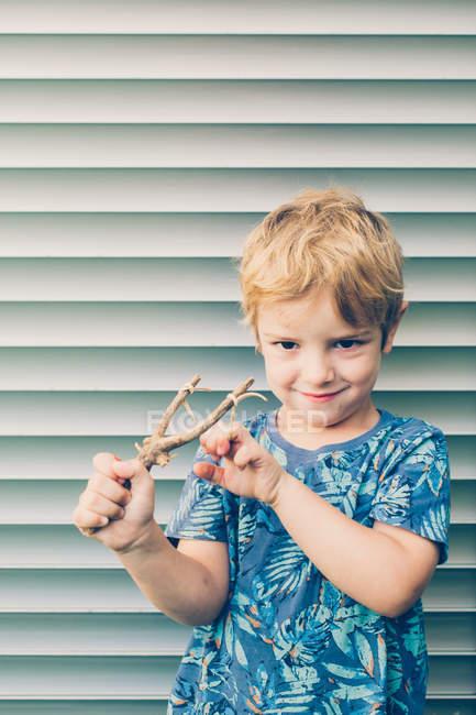 Biondo bambino in t-shirt giocare con fionda contro persiane — Foto stock