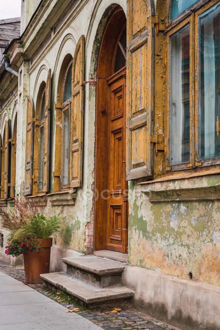 Pavimento de pedra e pequena porta perto da fachada do edifício grungy envelhecido na rua da pequena cidade — Fotografia de Stock