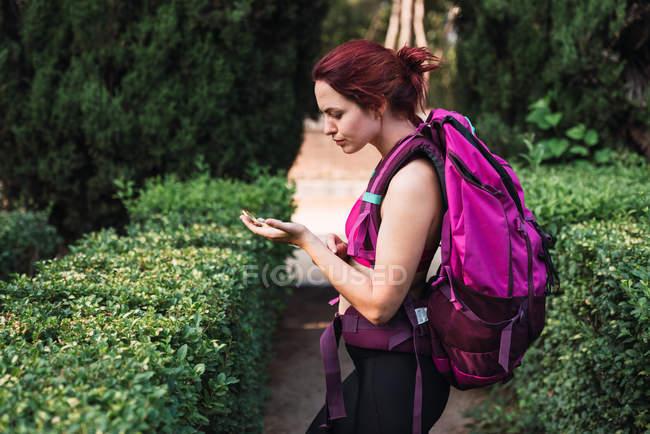 Donna in piedi in cespugli verdi nel parco con la bussola in mano — Foto stock