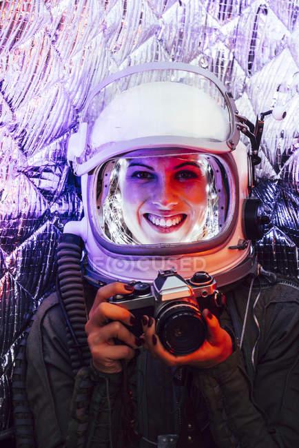 Menina vestindo capacete antigo espaço e traje segurando câmera de fotos — Fotografia de Stock