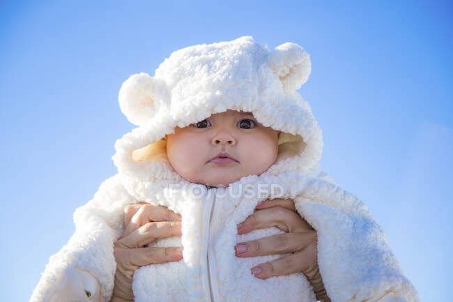 Hands of anonymous person holding adorable baby in warm clothes against cloudless blue sky — Stock Photo