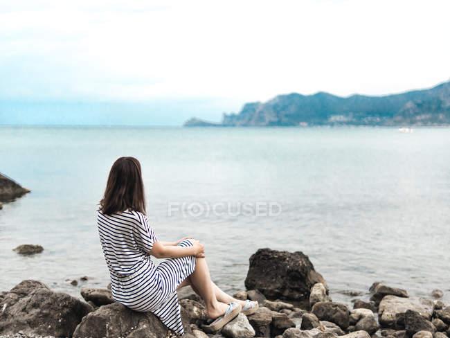 Мечтательная женщина сидит на скалистой береговой линии и смотрит на вид — стоковое фото