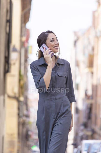 Cheerful woman speaking on smartphone on street — Stock Photo