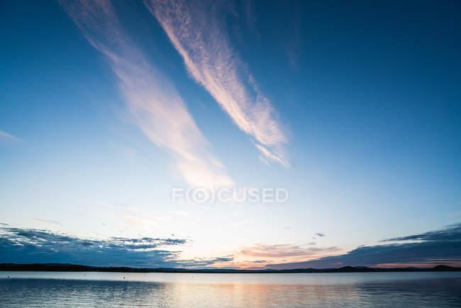 Superfície do tranquilo lago azul com céu dramático ao pôr-do-sol — Fotografia de Stock