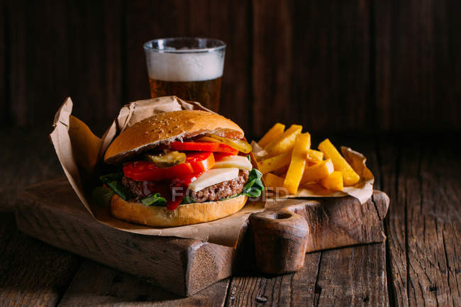Delicious gourmet burger with beer and fries on wooden board — Stock Photo