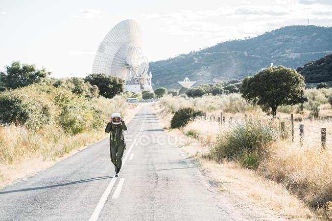 Mujer en traje de astronauta y casco caminando por la carretera en el campo - foto de stock